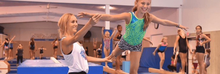 Gold Medalist Nastia Liukin helping a young gymnast on the balance beam at International Gymnastics Camp